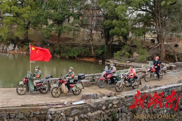 2月14日,临武县南强镇高安水村,镇防疫流动巡查队队员出发前往各村巡查。陈卫平 摄