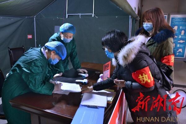 2月9日,由洪江市科协、芙蓉社区党员干部组成的防疫巡查小分队在市妇幼保健院了解进院就诊人员情况。 杨锡建 摄