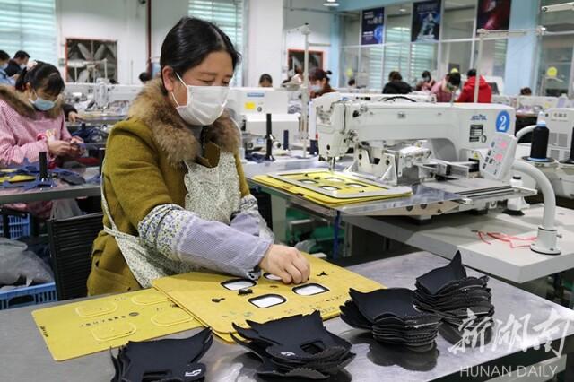 (3月9日,隆回县桃洪镇,湖南和亚运动用品有限公司扶贫车间,员工在忙着制鞋。罗理力 刘芳春 摄影报道)