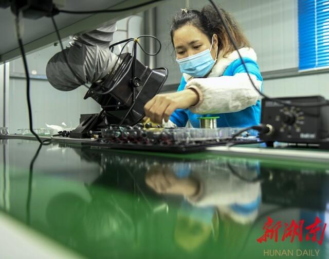 10月31日,道县横岭瑶族乡浪石村易地扶贫搬迁安置区扶贫工厂,工人在生产手机无线蓝牙耳机。蒋克青 摄