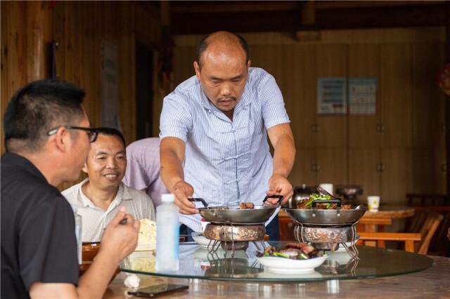 在湘西十八洞村,杨正邦(右)在给顾客上菜(6月30日摄)。新华社记者 陈思汗 摄