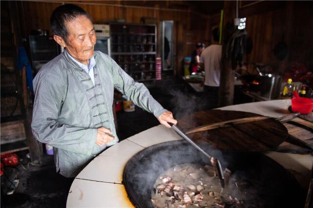 在湘西十八洞村,82岁的施成富在自家的农家乐里炒腊肉(6月29日摄)。新华社记者 陈思汗 摄