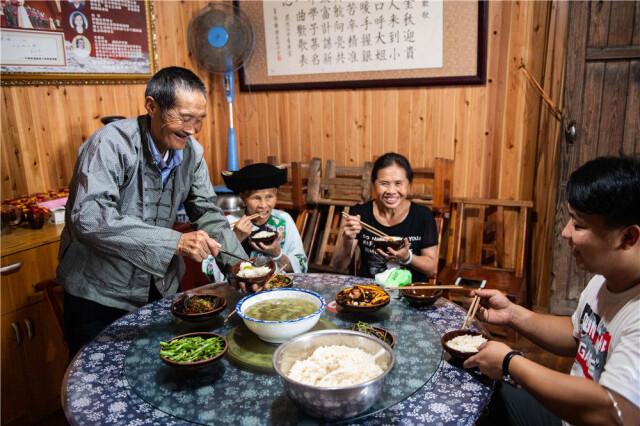 在湘西十八洞村,施成富(左一)和家人一起吃午餐(6月29日摄)。新华社记者 陈思汗 摄